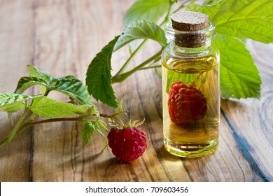 A bottle of raspberry seed oil with fresh raspberries on a wooden table