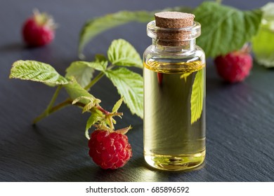 A bottle of raspberry seed oil with raspberries on a dark background