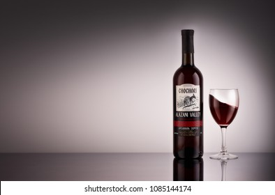 Bottle of red semi-sweet wine Chochori Alazani valley and glass of red wine on a grey background with reflection. Copy space. Georgian wine collection. Produced in Georgia.