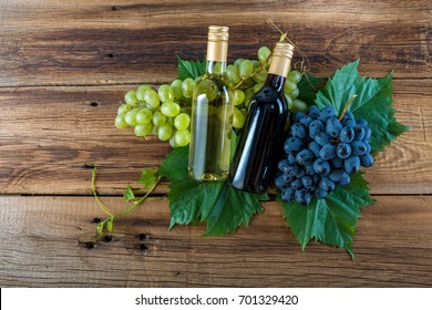 A bottle of red and white wine with grapes on a wooden background
