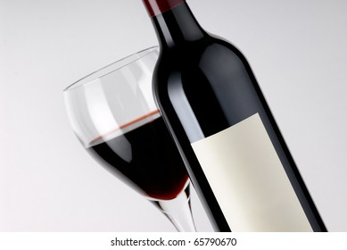 A bottle of red wine with a blank label stands in front of a filled glass.