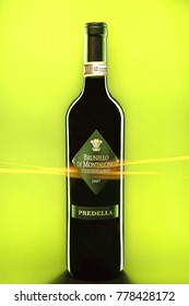 Bottle of red wine Brunello di Montalcino made in italy by Predella ,isolated on a yellow background with light flare in front.