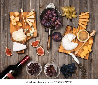 Bottle of red wine, cheese board, grapes,fig, honey and bread sticks on rustic wooden table, top view