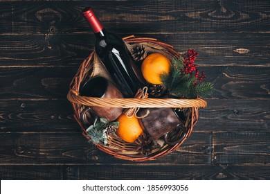 Bottle of red wine in Christmas gift basket. - Shutterstock ID 1856993056