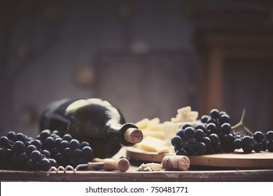 Bottle of red wine with a corkscrew On a  wooden background.