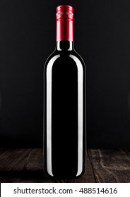 Bottle of red wine dark glass on wooden background red top