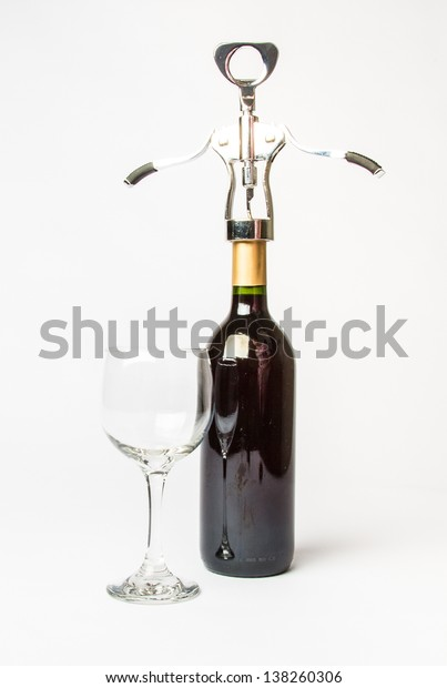 A bottle of Red wine, empty wine glass, and a cork screw on a white background.
