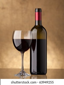 A bottle of red wine and filled with the same level of a wine glass on a golden background