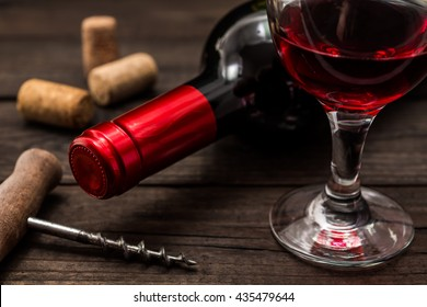 Bottle of red wine with a glass of red wine and corkscrew on an old wooden table. Close up view, focus on the bottle of red wine