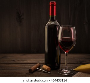 Bottle of red wine with a glass and corkscrew with a piece of parmesan on an old wooden table