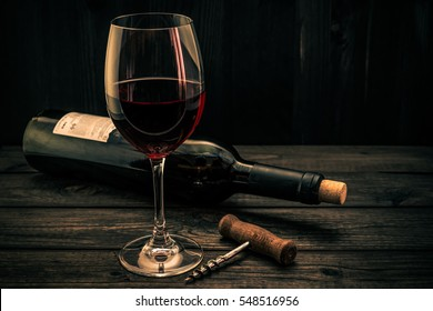 Bottle of red wine with a glass and corkscrew on an old wooden table. Focus on the corkscrew, image vignetting and the orange-blue toning