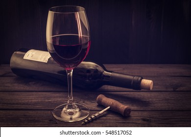 Bottle of red wine with a glass and corkscrew on an old wooden table. Focus on the corkscrew, image vignetting and the yellow toning