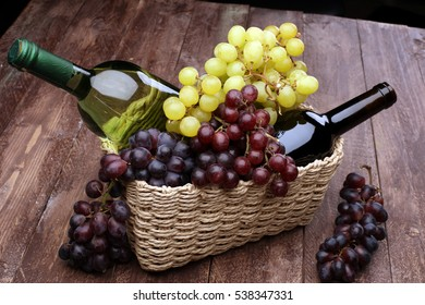 Bottle of red wine, glass and grape in basket in wooden interior.