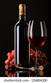 bottle of red wine, glass and grapes on dark background with place for text