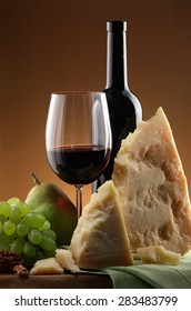 Bottle of red wine, glass of red wine, grapes and cheese still life