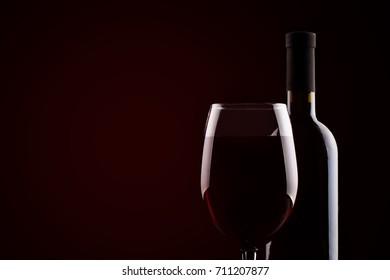 Bottle of red wine and a glass of red wine on a dark background.