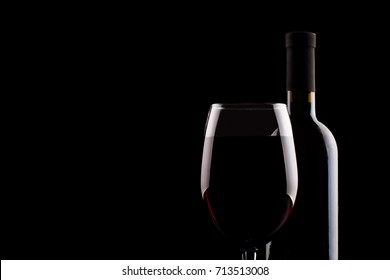Bottle of red wine and a glass of red wine on a black background.