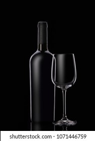 Bottle of red wine with glasses on black background