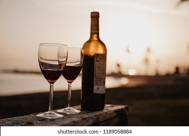 Bottle with red wine and glasses on the wooden, behind sunset