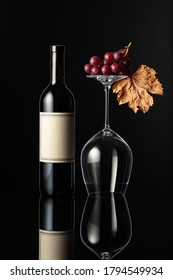 Bottle of red wine and an inverted wine glass on a black background. Wine with grapes and dried vine leaves. There's an old empty label on the bottle.