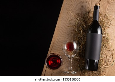 A bottle of red wine with a label on the old board. Glass of wine. A mock up bottle of wine. View from above. Flat lay. Space