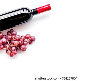 Bottle of red wine near bunch of grapes on white background top view copyspace