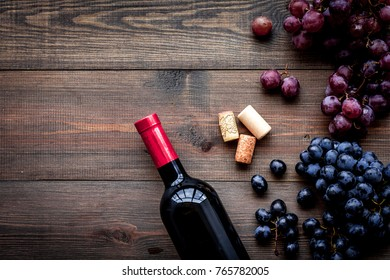 Bottle of red wine near bunch of grapes on dark wooden background top view copyspace