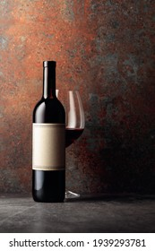 Bottle of red wine with old empty label on rusty brown background. Frontal view with space for your text.
