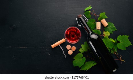 A bottle of red wine on a black wooden background. Grape. Free space for text. Top view.