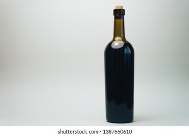Bottle of red wine on a old oak wooden table and gray background.