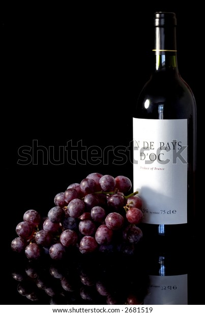 Bottle of red wine and some red grapes isolated against a black background with reflection