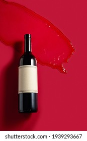 Bottle of red wine with splashes on a red background. Old empty label. Copy space.