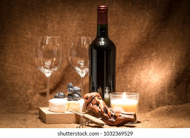 A bottle of red wine with two wine glasses, a french cheese, a corkscrew, and a candle
