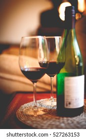 Bottle of red wine with two glasses on red table in dark romantic room candle light