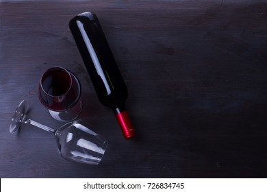 Bottle of red wine and two wine glasses on table with copy space