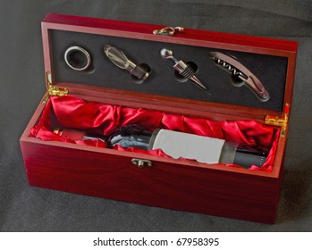 Bottle of red wine in a wooden box, with wine tools