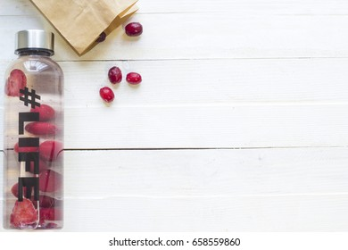 Bottle with refreshing drink, water with strawberry slices, with hash tag #life and package with frozen berries on white wooden background