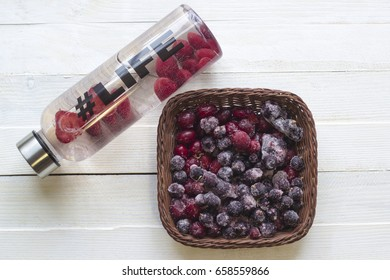 Bottle with refreshing drink, water with strawberry slices, with hash tag #life and basket with frozen berries on white wooden background