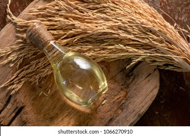 Bottle of rice bran oil and unmilled rice on wooden background.