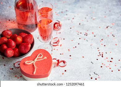 Bottle of rose champagne, two glasses with fresh ripe strawberries and heart shaped boxed gift, placed on stone table for a special romantic occasion or Valentines. With copy space