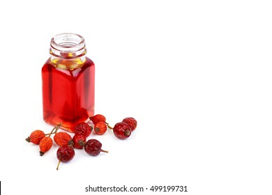 Bottle of rose hip oil on white background