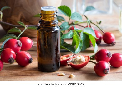 A bottle of rose hip seed oil on a wooden table, with fresh rose hips in the background