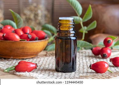 A bottle of rosehip seed oil with fresh hips