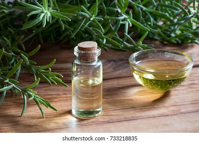 A bottle of rosemary essential oil with fresh rosemary twigs on a wooden background