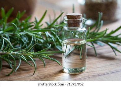 A bottle of rosemary essential oil with rosemary twigs on a wooden background