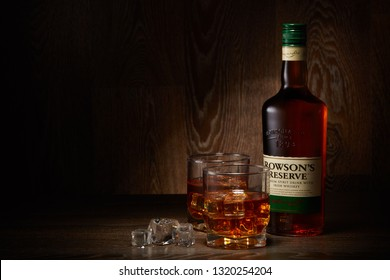 Bottle of Rowson's Reserve whisky and two glasses of whisky with ices standing on a wooden table on a dark background with copy space. Premium spirit drink with irish whiskey