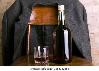 Bottle of rum and old-fashioned glass on the retro wooden chair, male coat on it