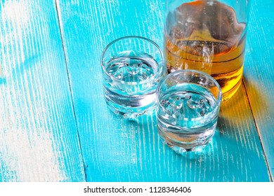 the bottle of rum on the blue table there are two empty cups