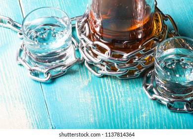 a bottle of rum and two glasses next wrapped with a metal chain, a wooden background