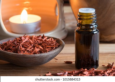 A bottle of sandalwood essential oil with sandalwood pieces and an aroma lamp in the background